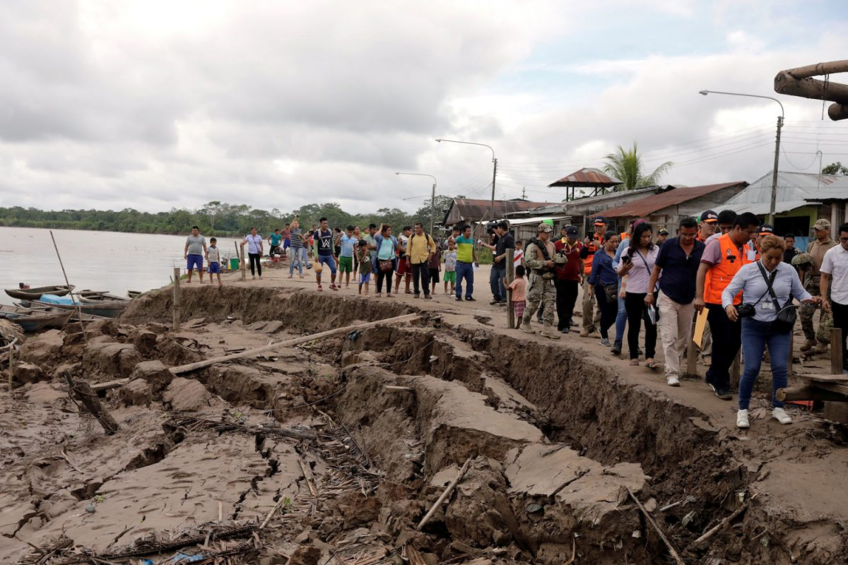 Government officials and media tour an area affected by a quake