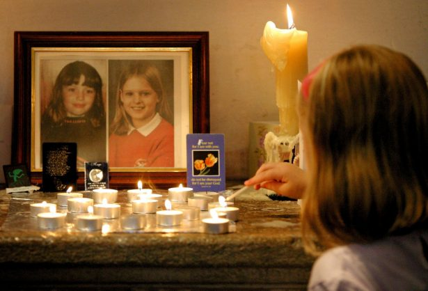 A young girl lights a candle