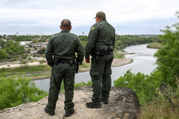 Border Patrol agents overlook the Rio Grande towards Mexico on the Roma Bluffs