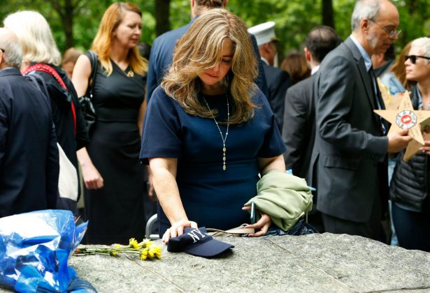 Woman touching the stone at the 9/11 memorial glade. (9/11 Memorial & Museum, photo by Monika Graff)