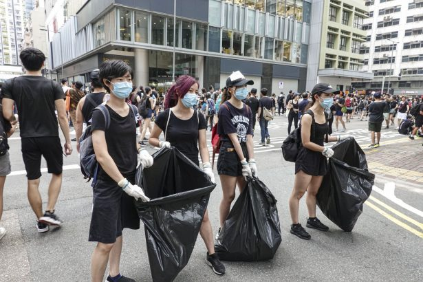 Anti-extradition protesters help collect trash during the protest on June 16, 2019. (Yu Gang/The Epoch Times)