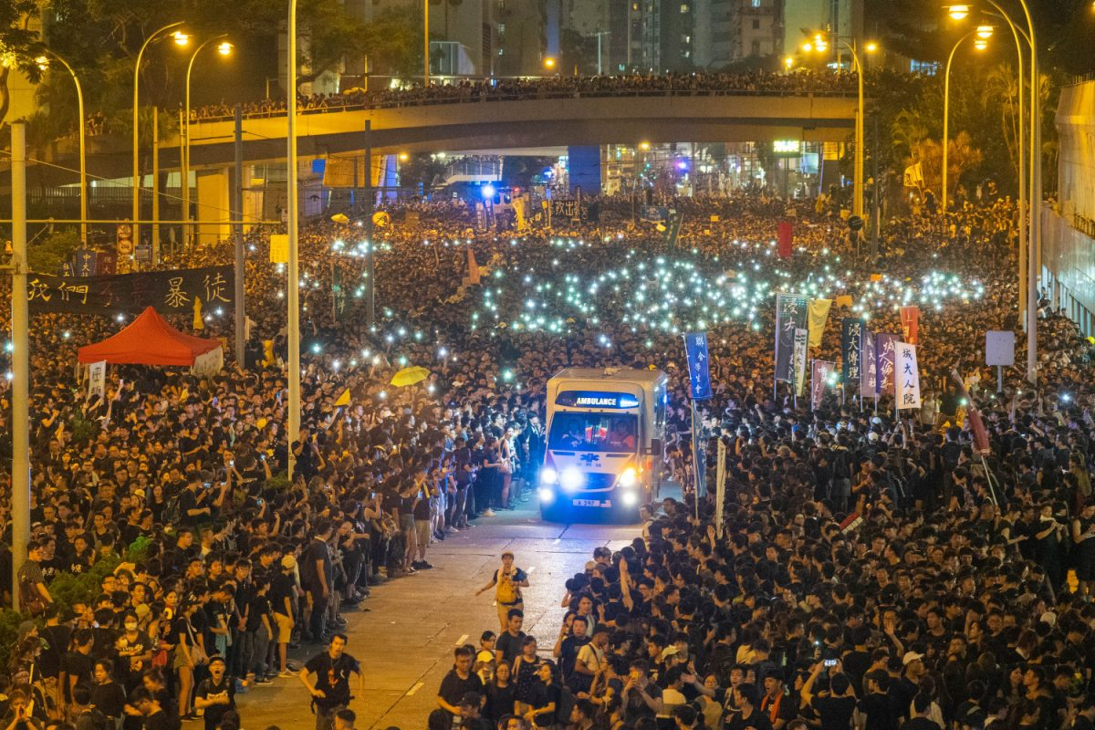Crowds part way to let ambulances and buses through. Some say the scene reminds them of Moses and his people crossing the red sea. (Song Bilong/The Epoch Times)