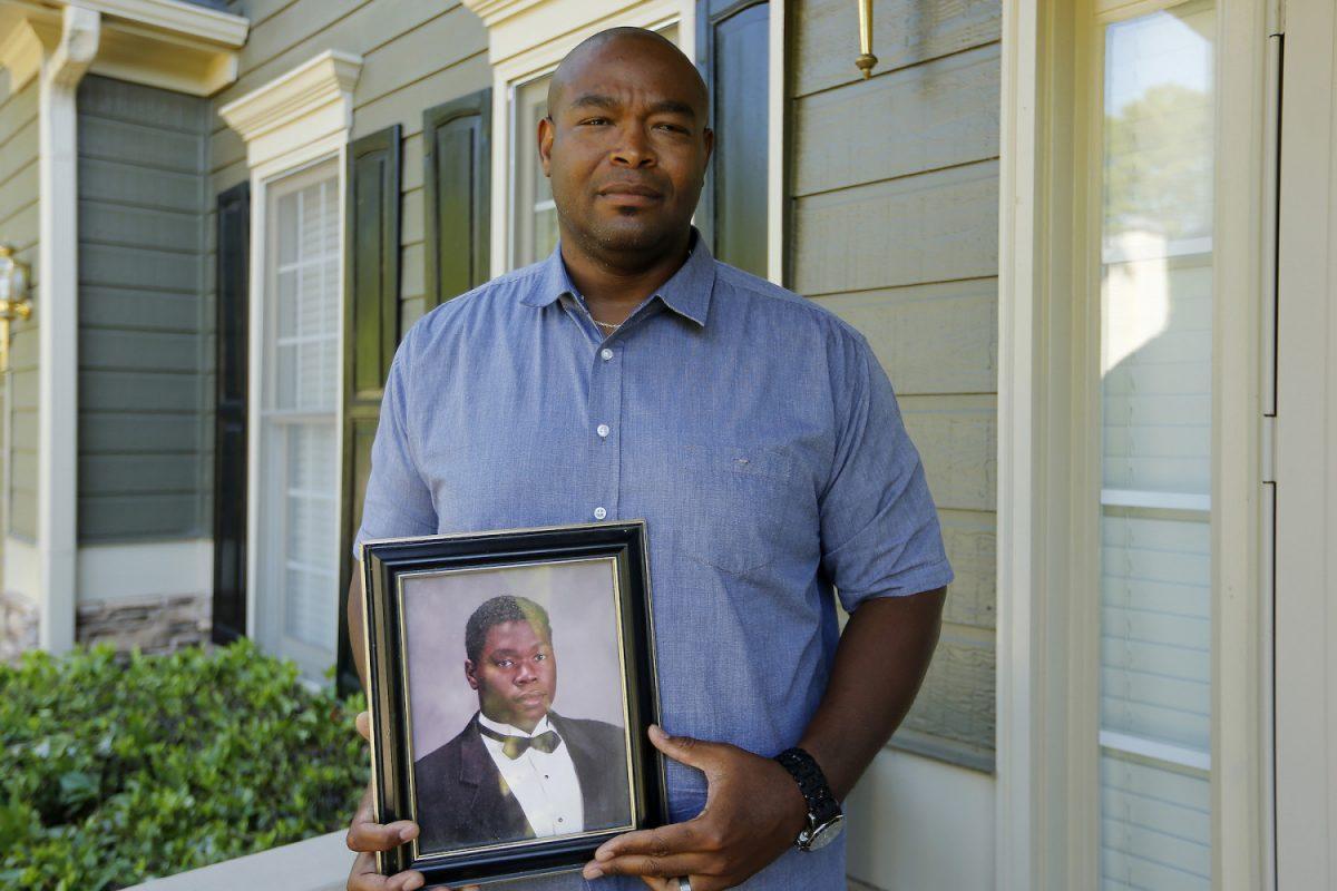 Chris Parks poses with a portrait of Donovan Corey Parks 1