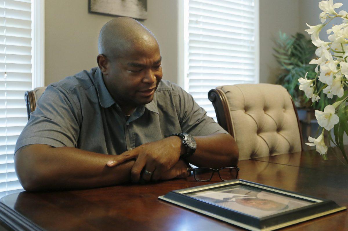 Chris Parks poses with a portrait of Donovan Corey Parks