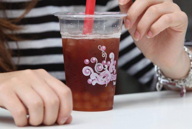 A young woman sips bubble tea