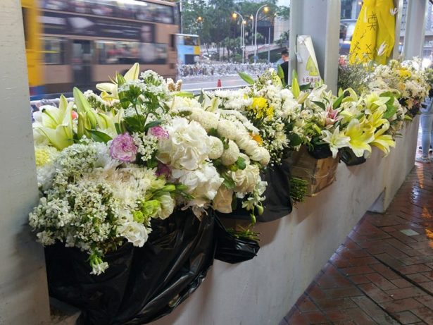 After cleaning up the flowers put out to memorialize a Hong Kong student who died during the protest, volunteers used the flowers to decorate the streets.(Courtesy to Florence Hui)