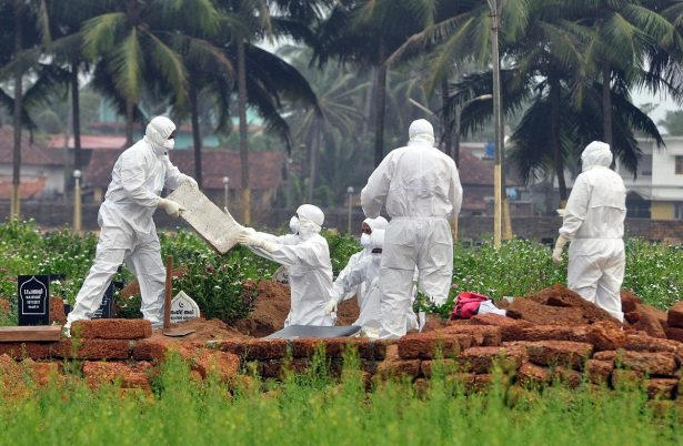 Doctors and relatives wearing protective gear dig a grave to bury the body of a Nipah virus victim