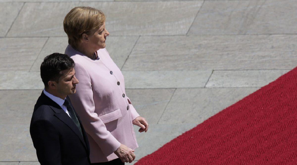 German Chancellor Angela Merkel, right, and Ukrainian President Volodymyr Zelenskiy, left, listen to the national anthems during the welcoming ceremony, prior to a meeting