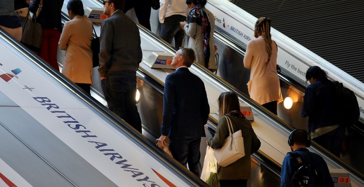 Commuters pass a British Airways advert on the tube