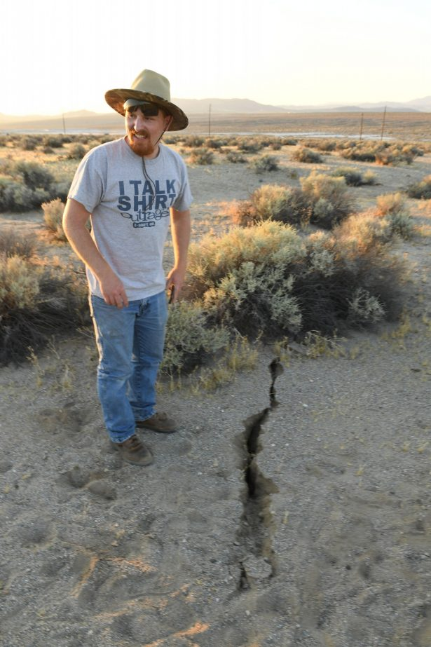 People Take Pictures Near and Inside Cracks Left by