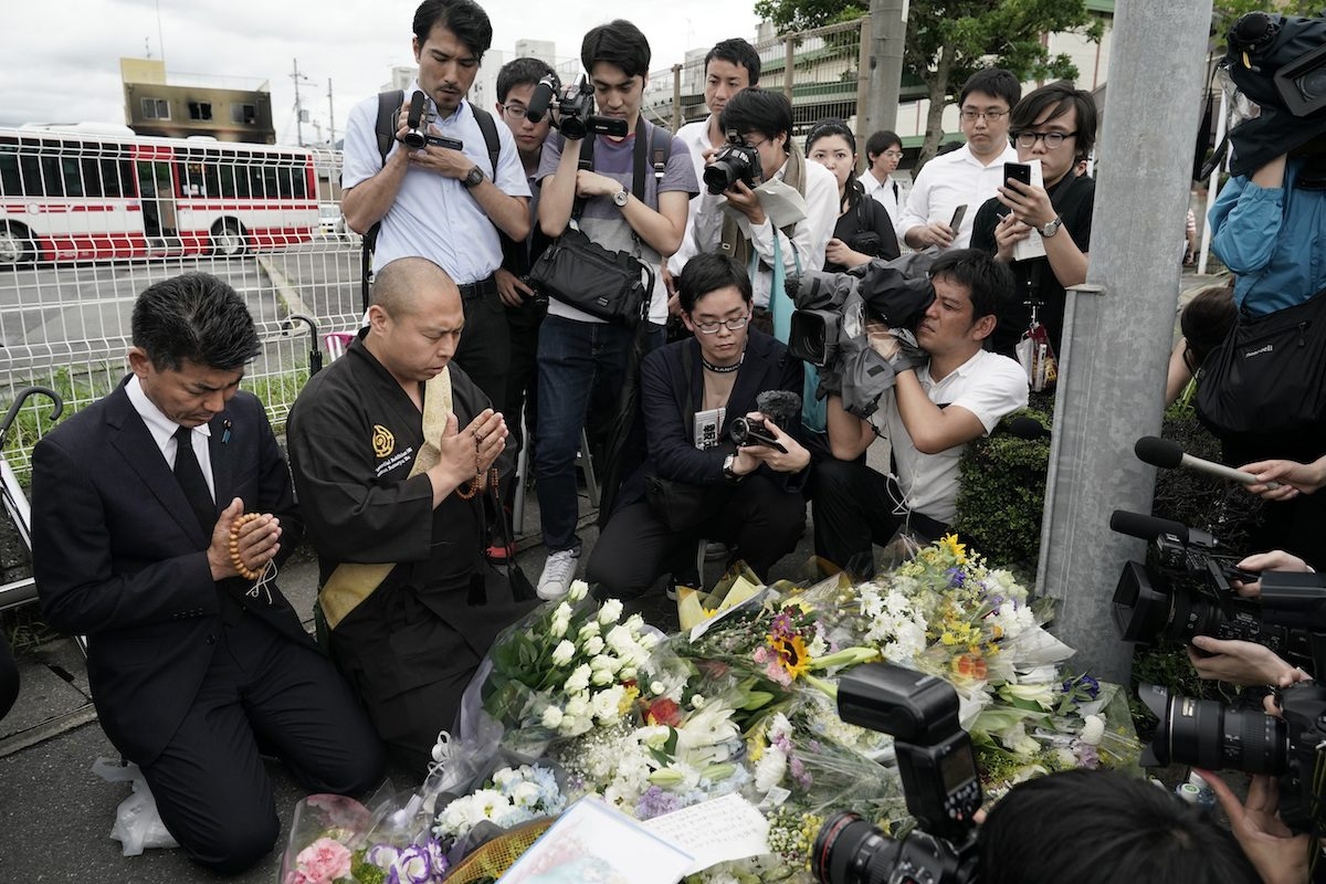Japanese Diet member, Kenta Izumi (L), and Buddhist monk, Matsumoto Genkun, pay respects at a makeshift memorial site in front of burned Kyoto Animation Studio, on July 19, 2019, in Kyoto, Japan. (AP Photo/Jae C. Hong)