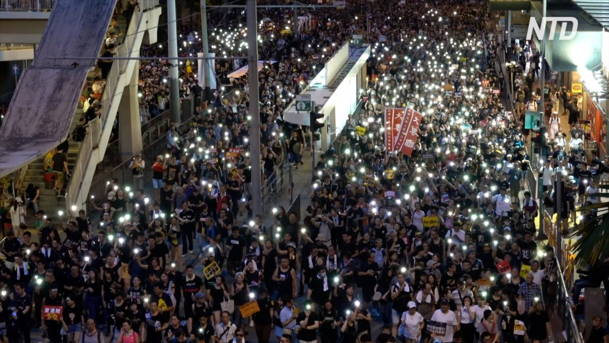 Protesters use the flashlights from their phones as they march on July 1, 2019. (NTD)