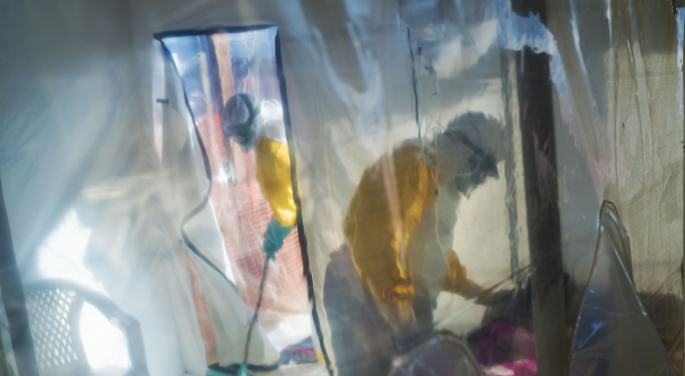 Health workers wearing protective suits tend to to an Ebola victim kept in an isolation