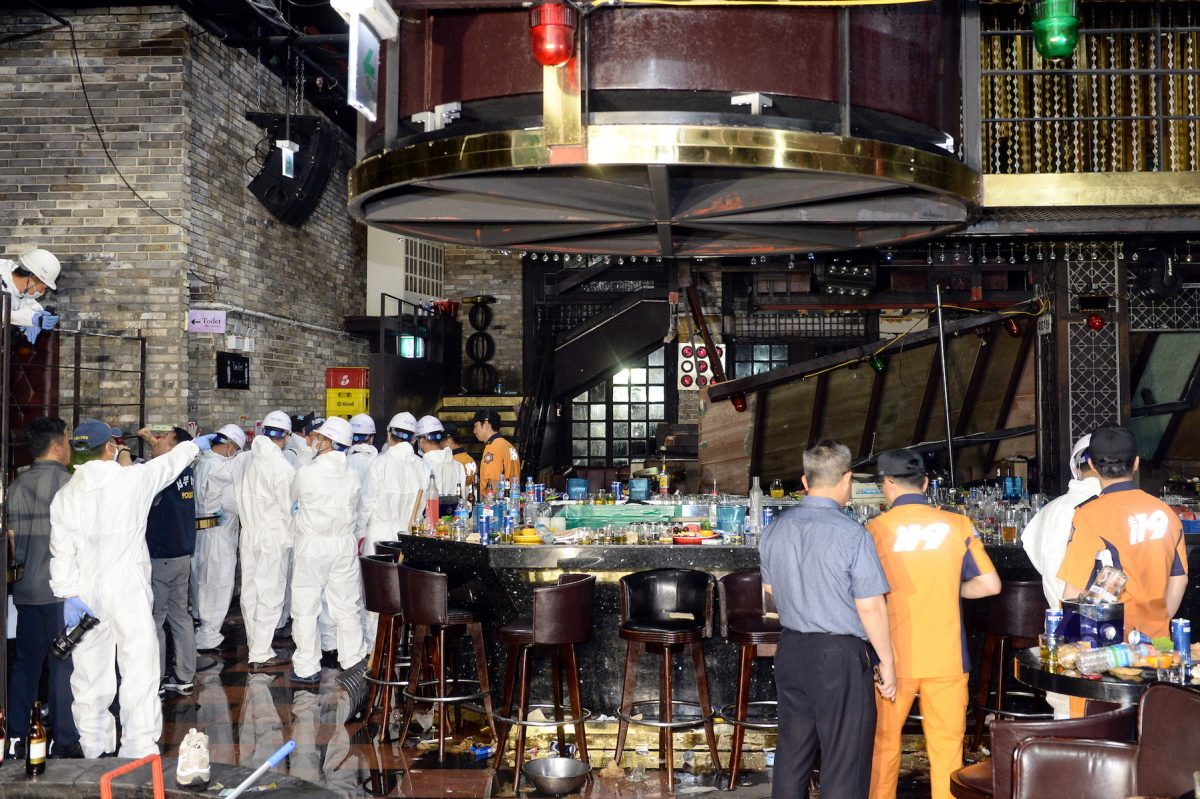 South Korean firefighters and officials examine the collapsed structure of a nightclub in Gwangju