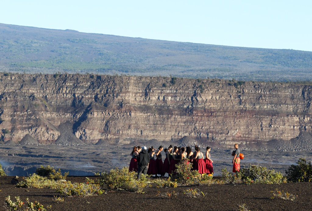 A group of Native Hawaiians stand next to the collapsed caldera floor of Kilauea volcano