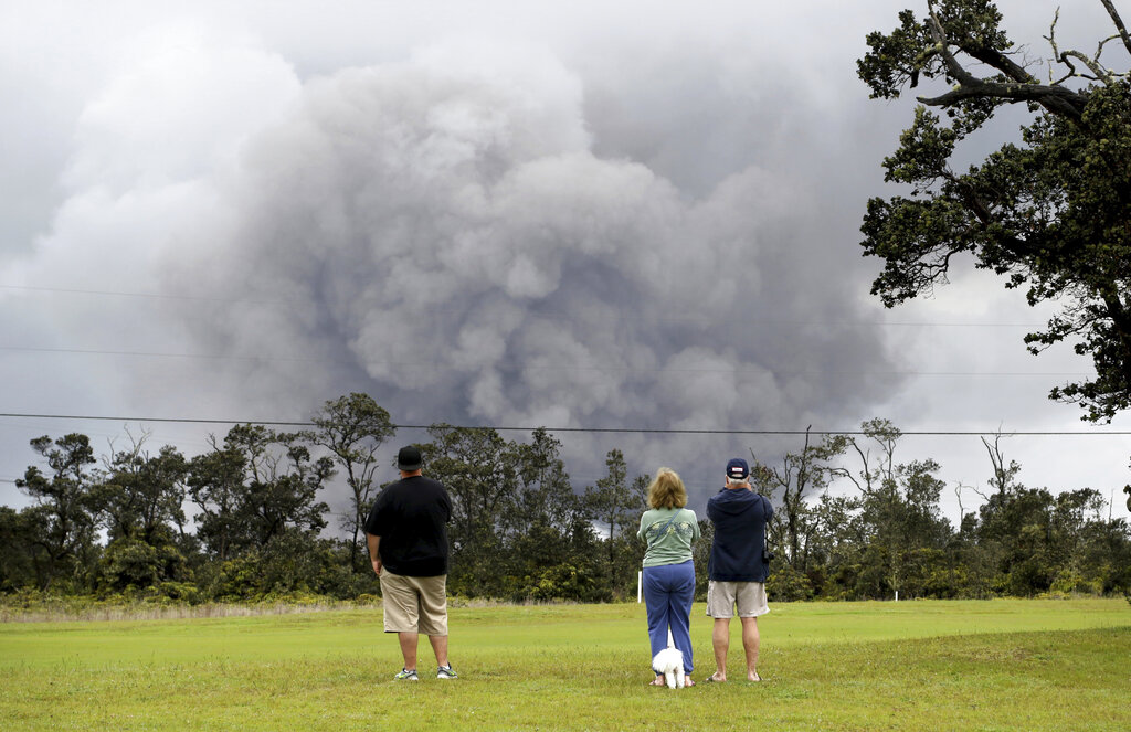People watch ash and debris explode from the summit crater of Kilauea