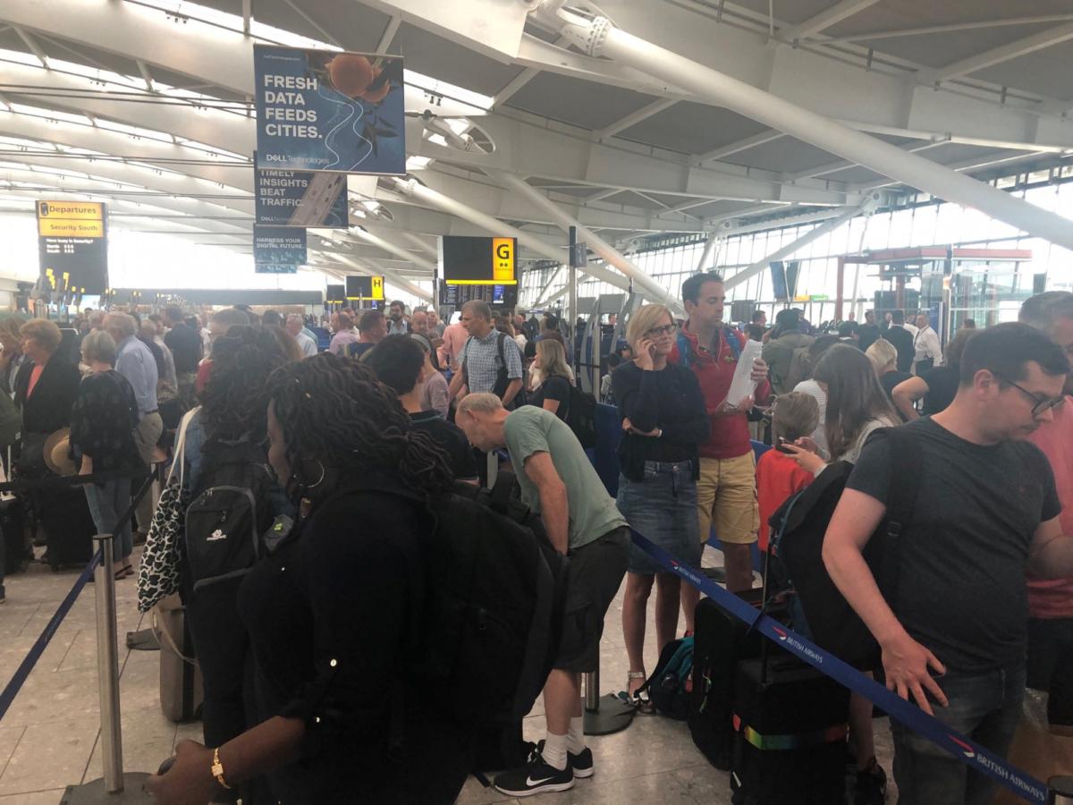 Passengers wait in long queues