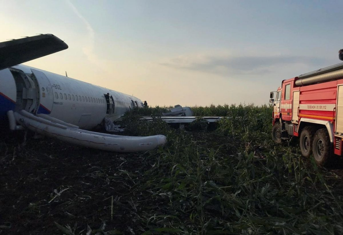 A fire fighting vehicle is parked near the Ural Airlines Airbus 321 passenger plane