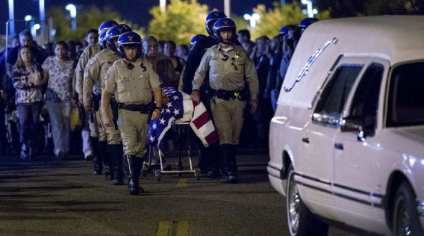 The casket of slain CHP officer Andre Moye is transported to a hearse from the Riverside