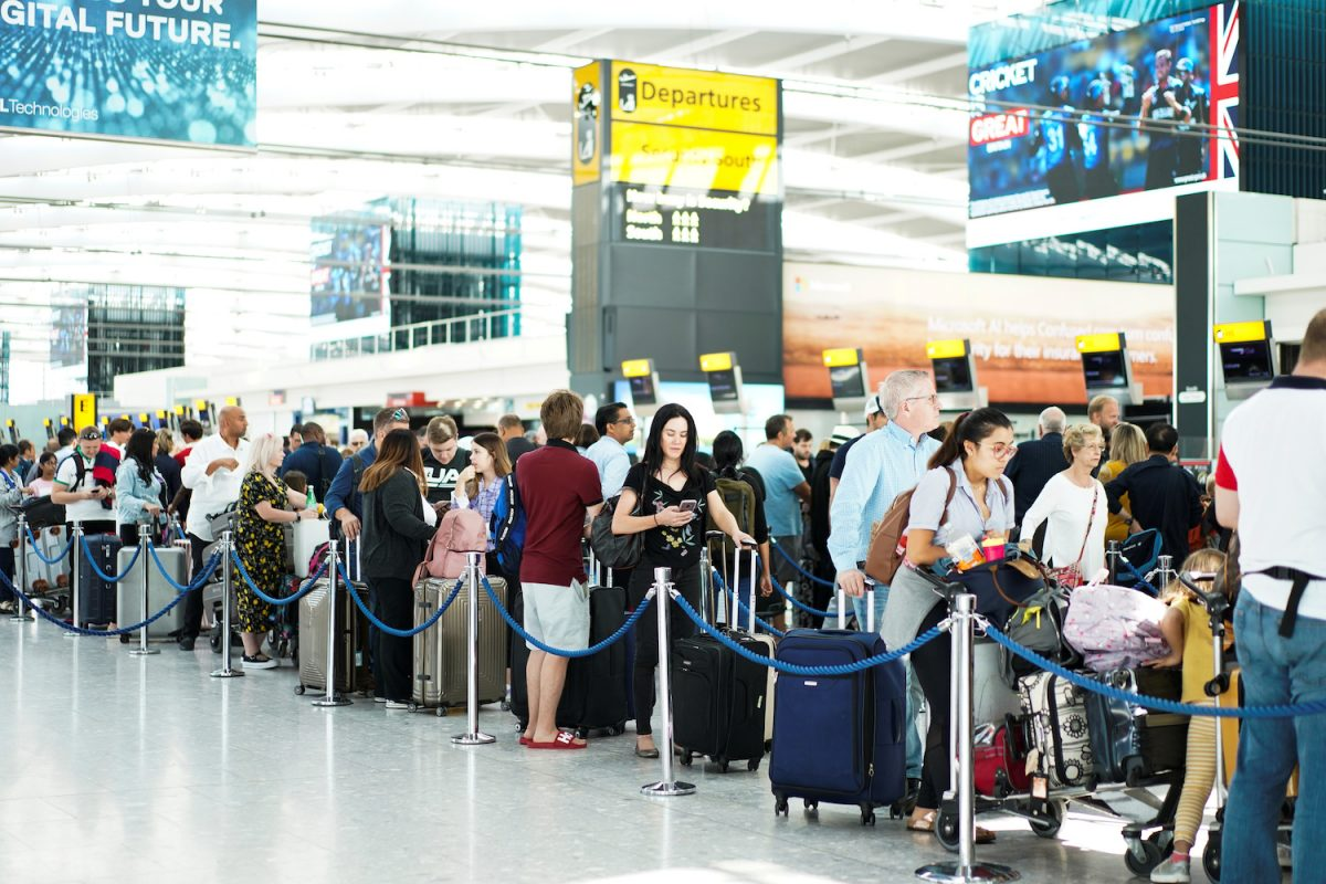 People queue inside Terminal 5 at Heathrow Airport as IT problems caused delays in London