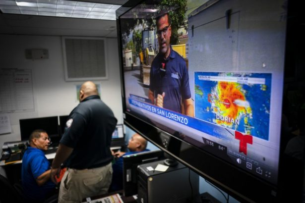 Emergency Center personnel stand next to a tv screen showing a meteorological