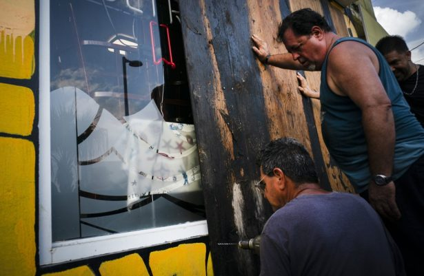 Men board up a shop's windows ahead of the arrival of Tropical Storm Dorian