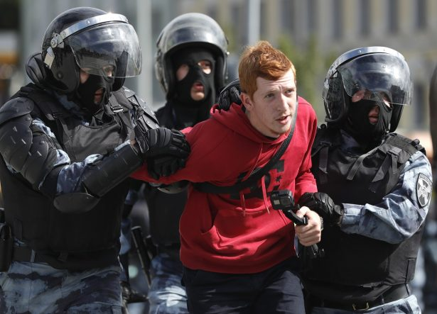 Police officers detain a protestor during an unsanctioned rally in the center of Moscow,