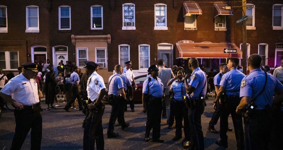 Officers gather for crowd control near a massive police presence set up outside a house