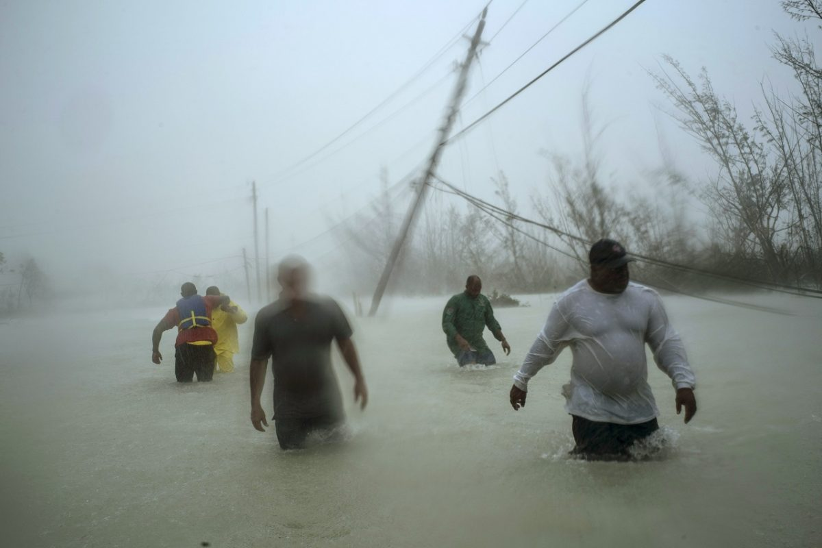 Volunteers walk under the wind and rain from Hurricane Dorian