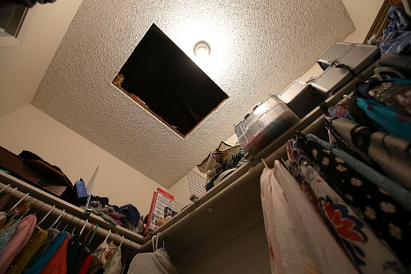 A hole in the ceiling is visible in a bedroom closet inside the home of shooting