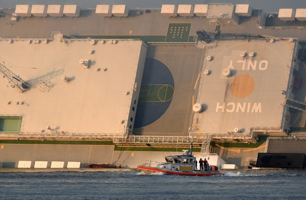 A U.S. Coast Guard boat rides in front of a cargo ship that capsized in the St. Simons Island sound, Ga.