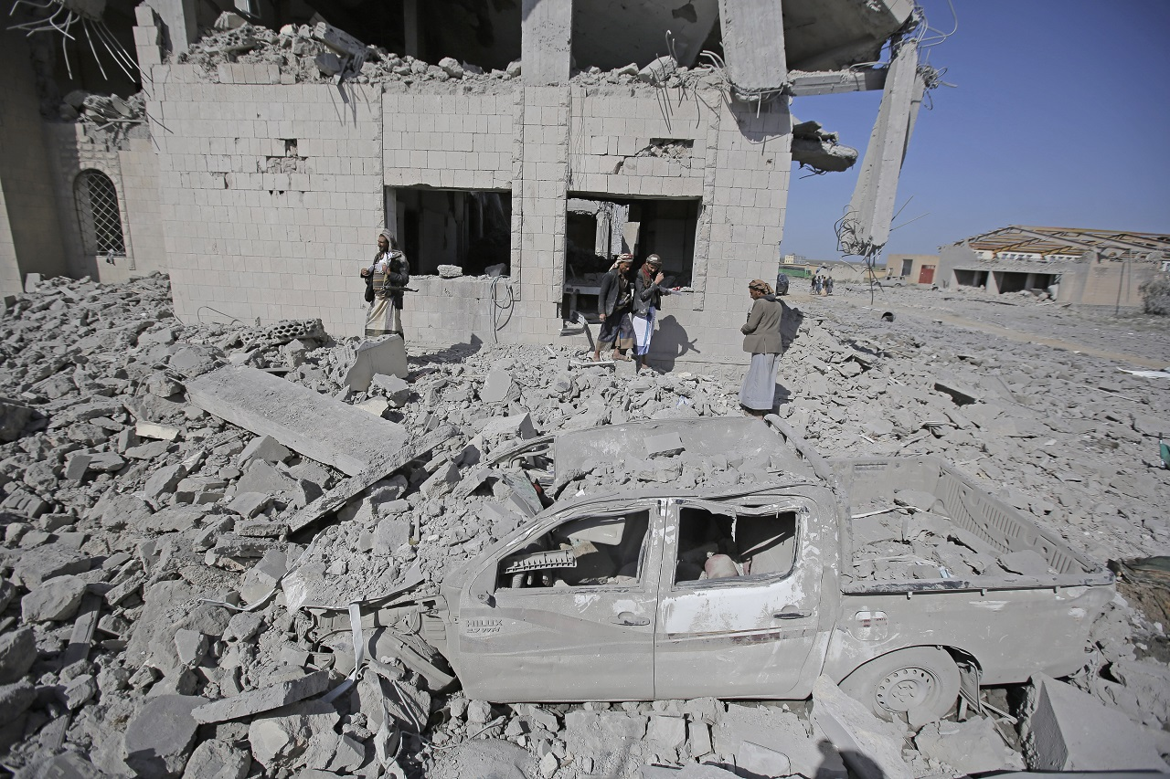 People inspect a Houthi detention center destroyed by Saudi-led airstrikes,
