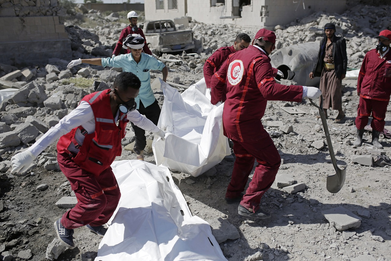 Rescue workers recover bodies from under the rubble of a Houthi detention center destroyed by Saudi-led airstrikes,