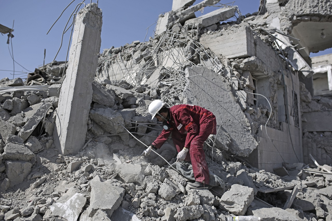 A rescue worker uncovers the body of a detainee from under the rubble of a Houthi-held detention center destroyed by Saudi-