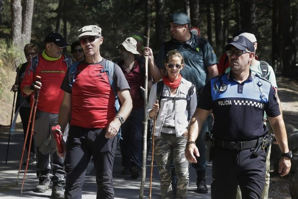 Volunteers walks with a civil guard and a police officer after searching