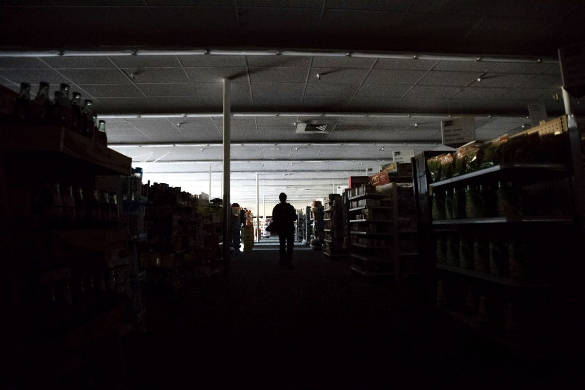 Shift supervisor James Quinn walks through a darkened CVS Pharmacy as downtown Sonoma, Calif., remains without power on Wednesday, Oct. 9, 2019. (Noah Berger/ AP Photo)