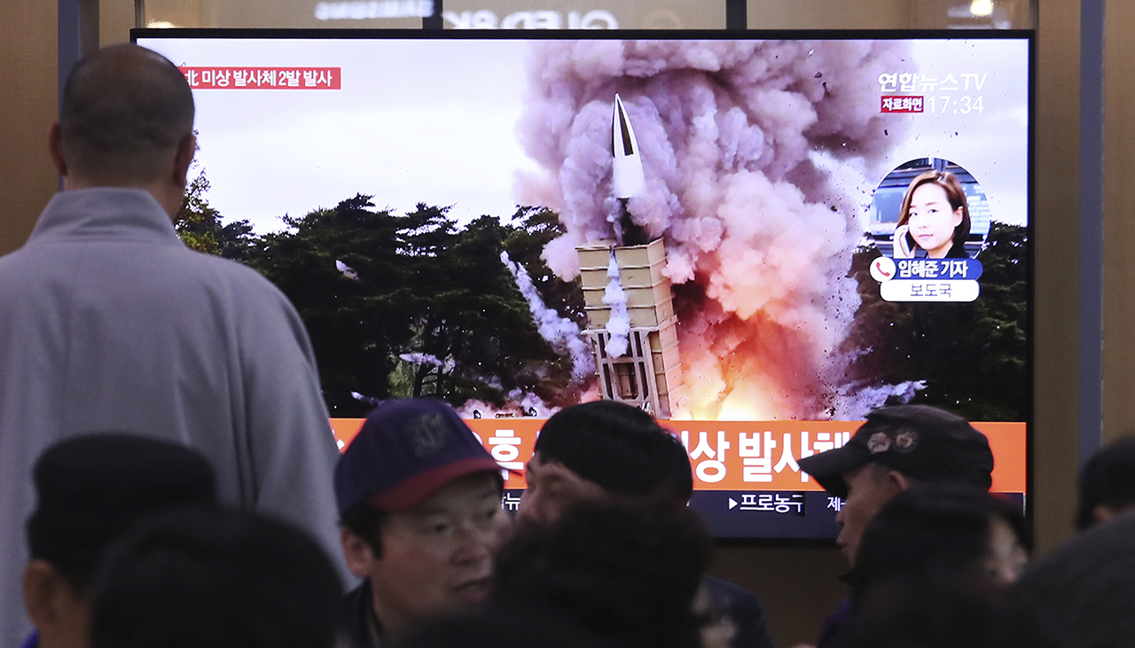 People watch a TV showing a file image of an unspecified North Korean missile launch