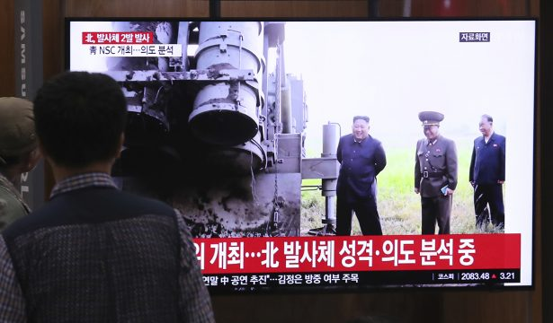 People watch a TV showing a file image of North Korean leader Kim Jong Un