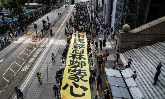People march to protest against what they say is the abuse of pro-democracy protesters by Hong Kong police, near Chater Garden in Central district