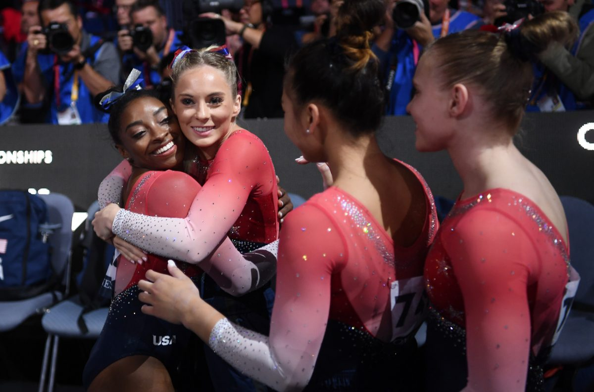 Simone Biles of USA is congratulated by her team