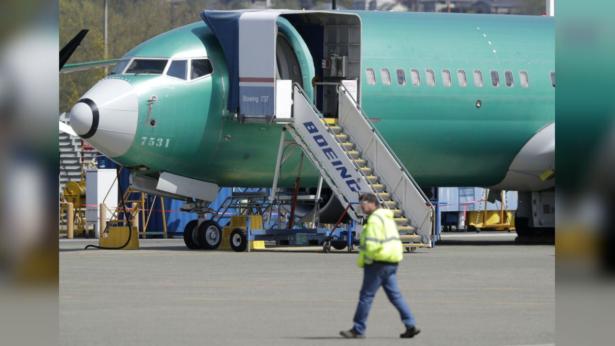 Worker walks past a Boeing 737