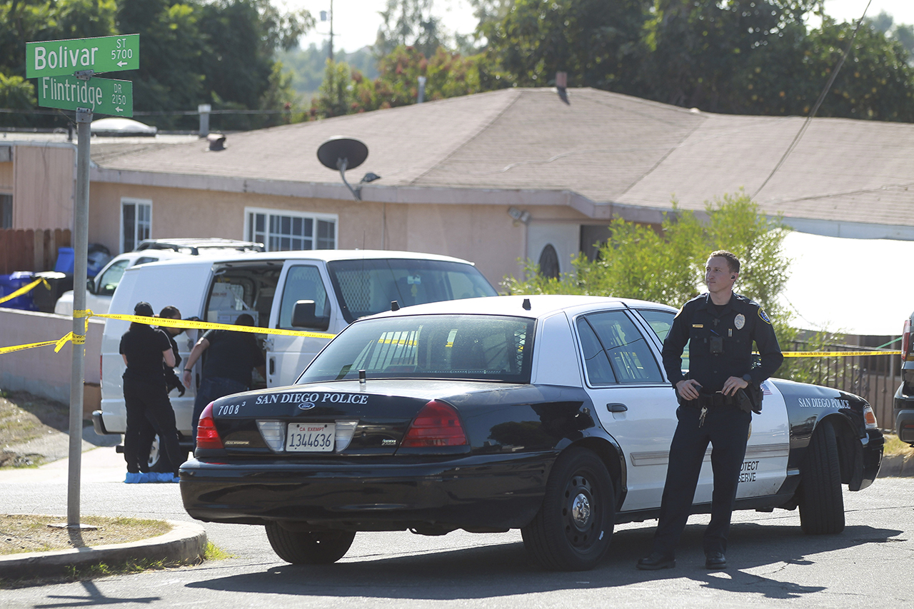 A San Diego Police officer stands in front of a home where two adults and three children died