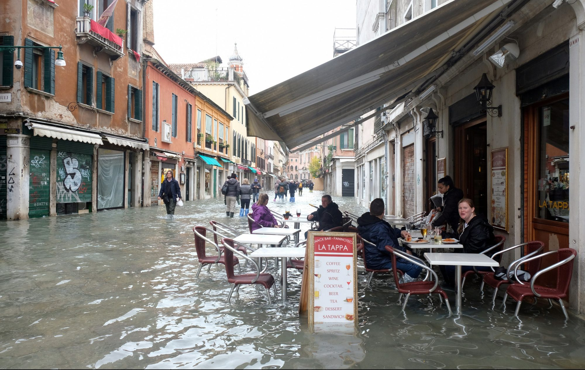 People sit at a cafe in a flooded street