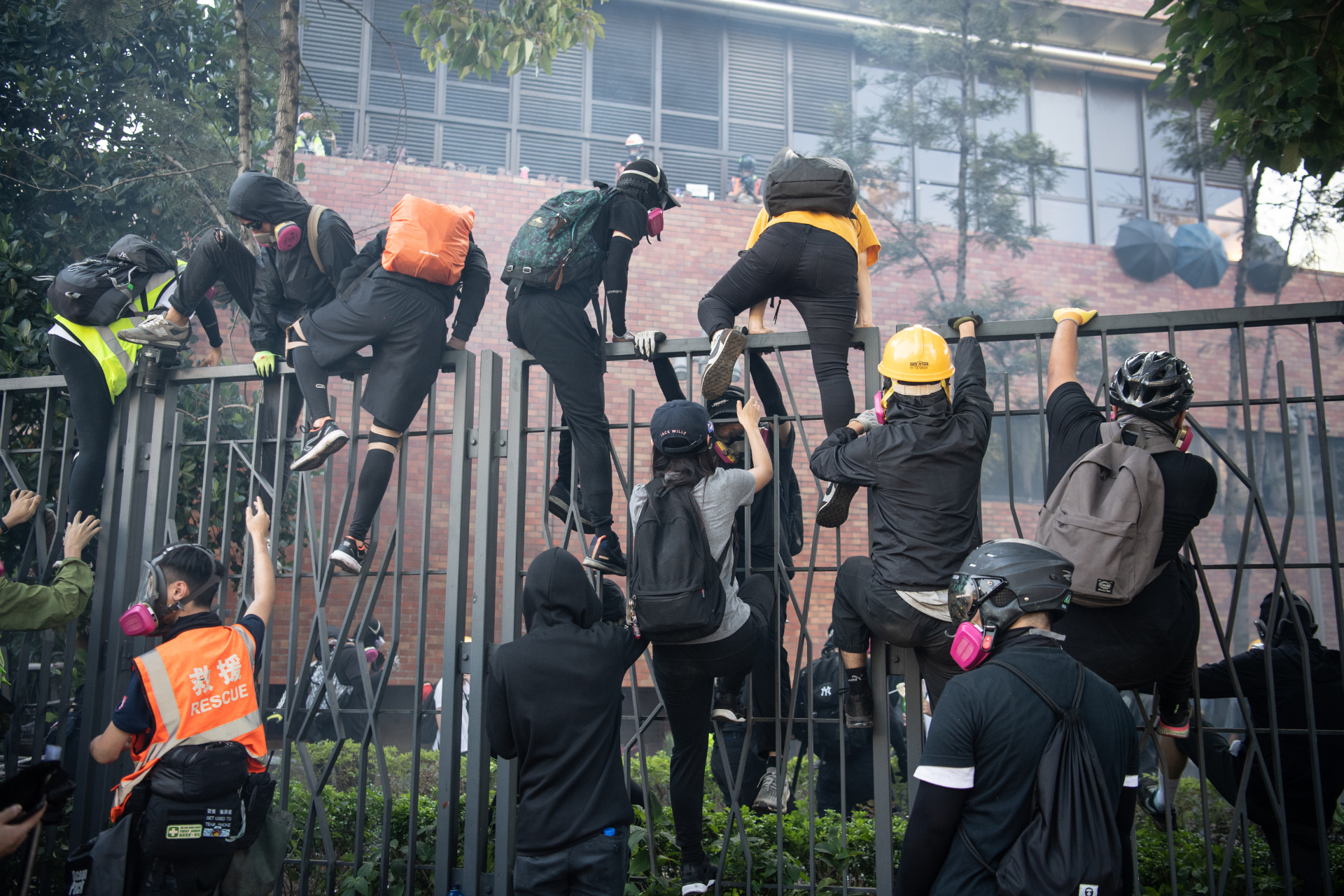 Protesters climb over fences
