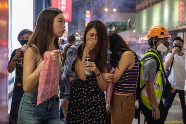Pedestrians react after police fired tear gas
