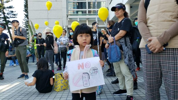 A girl holds a scatch showing no to tear gas