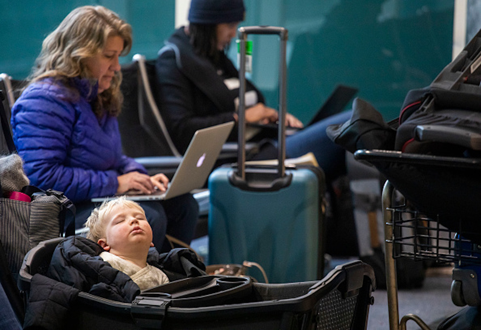 Two-year-old Mile Feiger, of Seattle, naps amid his familys bags and other travelers at Denver