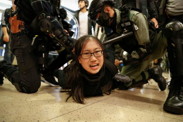 Police officers detain an anti-government protester