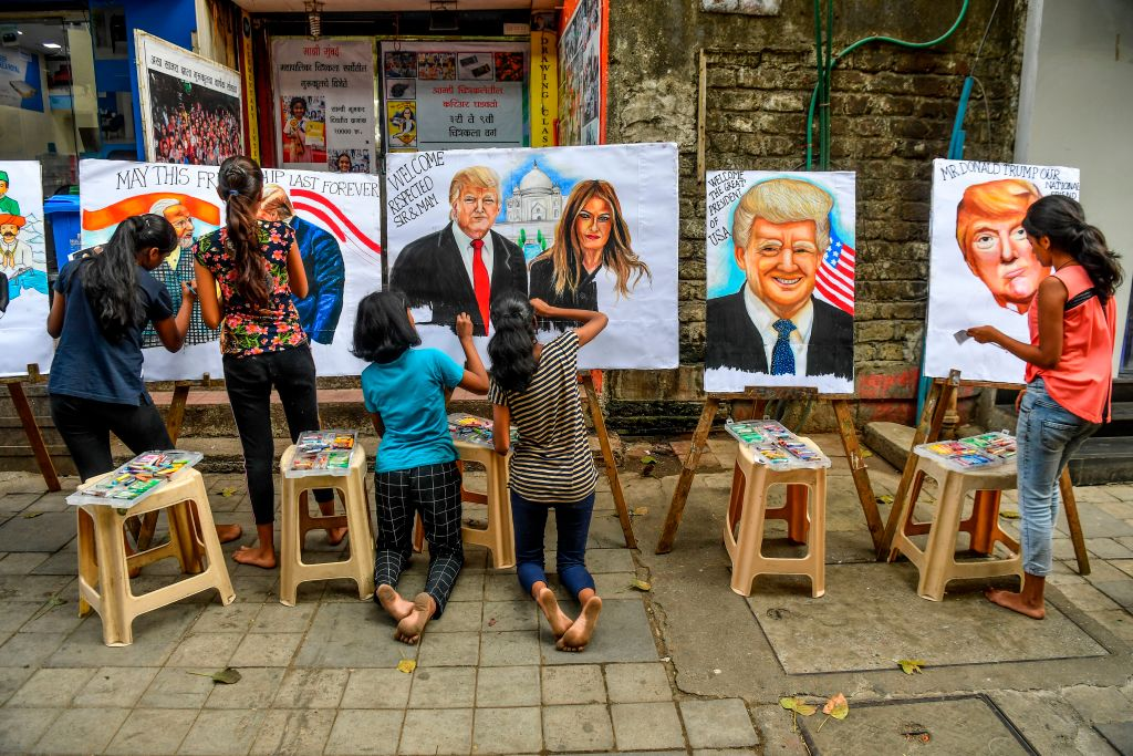 Students paint on canvas faces of President Donald Trump, First Lady Melania Trump and Modi