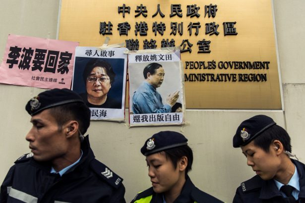 Police walk past missing person notices of Gui Minhai
